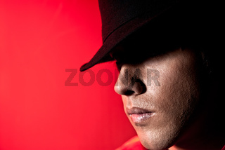Handsome man portrait hat dark eyes mistery concept red background