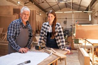 Handwerksmeister und junge Frau als Lehrling