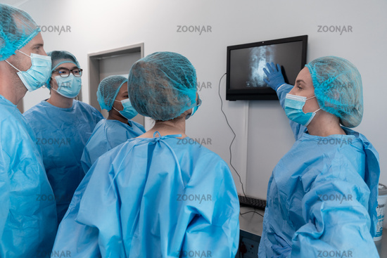 Diverse group of male and female surgeons in operating theatre wearing face masks looking at screen