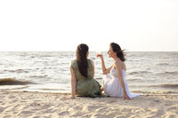 Happy adult women with wine resting on beach