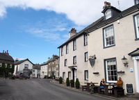 people outside the priory hotel near the village square and shop in cartmel cumbria