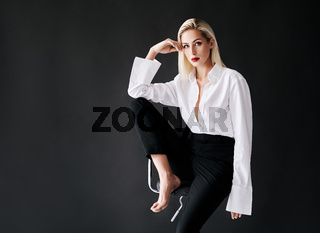 Young stylish woman posing on the chair on black studio background