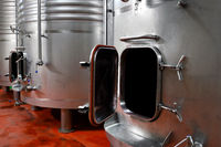 Industrial stainless steel vats in modern brewery.