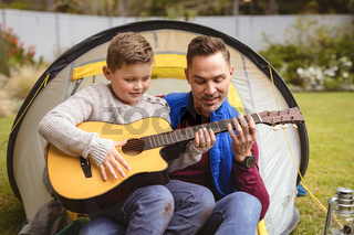 Caucasian father and son playing guitar together while sitting in a tent in the garden