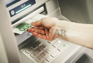 Close op of young woman withdrawing money from an atm