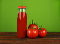 Bottle of ketchup and fresh tomatoes over green
