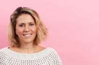 Pretty mature woman in front of pink background