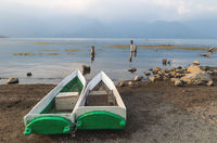 Traditional fishermen canoes at the shore along lake Atitlan during sunset in San Pedro la Laguna, Guatemala