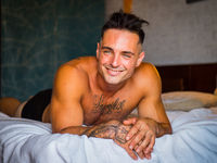 Shirtless male model lying alone on his bed smiling