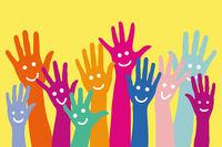 Bunte Hände mit Smiley vor gelbem Hintergrund
