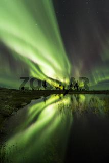 Nordlicht (Aurora borealis) spiegelt sich in einem Bergsee, Lappland, Schweden