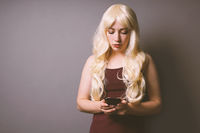 serious young woman using smartphone reading bad news text message