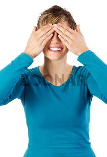 Lachende Frau verdeckt ihre Augen