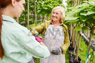 Seniorin als Gärtner und Gärtner Azubi beim handshake