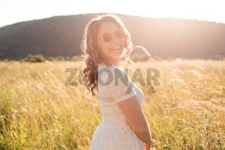 The joyful young woman in sunglasses pleasure nature