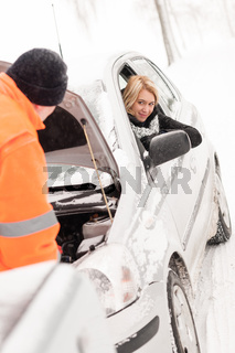 Man repairing woman's car snow assistance winter