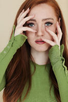 Redhead woman touching face