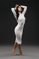 Slender woman in white dress in studio