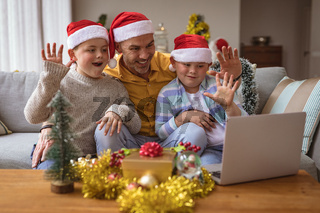 Caucasian father and two sons waving while having a video call on laptop at home during christmas