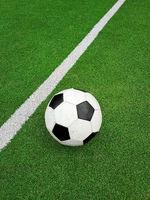 Football ball over green soccer field