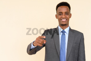 Portrait of handsome African businessman wearing suit and tie against plain background while smiling and pointing finger