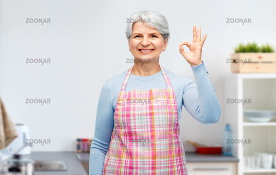 smiling senior woman showing ok gesture at kitchen