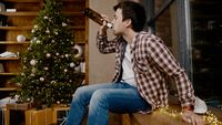 Problems of alcoholism in loneliness, sadness and melancholy during pandemic covid 19. Male removes mask from coronavirus, drinking wine from bottle during new year holidays sitting by Christmas tree