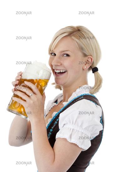 Hübsche junge blonde Frau im Dirndl trinkt aus Oktoberfest Mass Bier