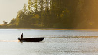 Idyllic calm soothing morning scenery at mountain lake Walchensee in Bavaria, Germany at dawn with man standing in fishing boat