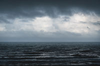 Melancholic dark blue seascape with silver shining waves during storm