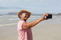 Happy senior african american woman taking a selfie from smartphone on the beach