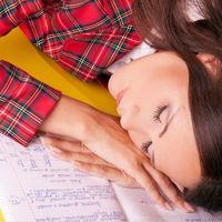 Closeup of beautiful girl sleep on the notebook.