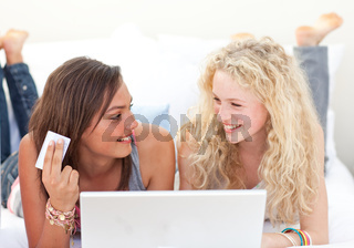 Brunette and blonde girls shopping online in a bedroom