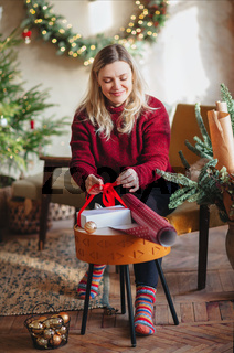 Smiling woman sitting on chair in new year festively decorated living room and packing xmas gift box