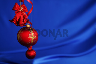 red christmas balls on blue satin background