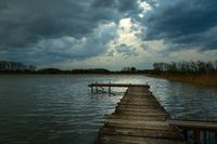 Wooden pier on a lake and dark clouds on the sky