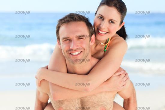 Man having wife a piggyback on the beach