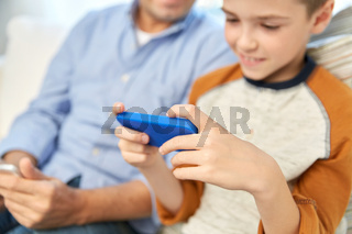 father and son with smartphones at home