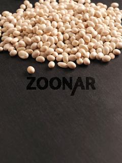 A heap of organic white beans on a blackboard with space for your text or image