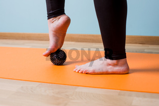 Massaging bare feet with small knobbed ball
