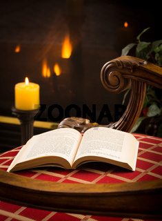 Paperback book open on chair by fire and candle