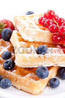 Frische süße Waffeln mit Puderzucker und beeren auf einem Teller isoliert auf weiß