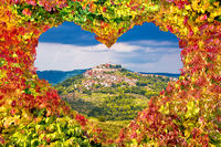 Historic town of Motovun on green hill view through heart shaped autumn leaves