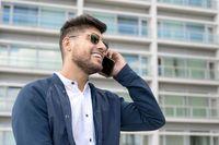 Handsome Man talking on cellphone outside modern office building.