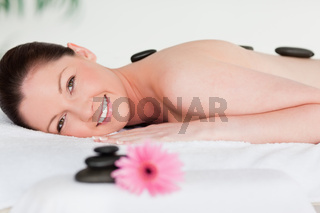 Happy young woman with massage stones and a pink gerbera
