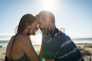 Happy caucasian couple on the beach touching foreheads