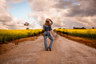 Aussie country girl standing on dirt road in farm fields