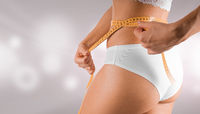 Young woman body in white lingerie. Diet concept with measuring tape. Healthy skin