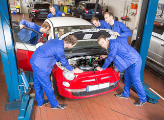 Kfz Mechaniker in Werkstatt bei der Reparatur eines Autos