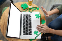 Caucasian woman waving making st patrick's day video call with laptop at a bar